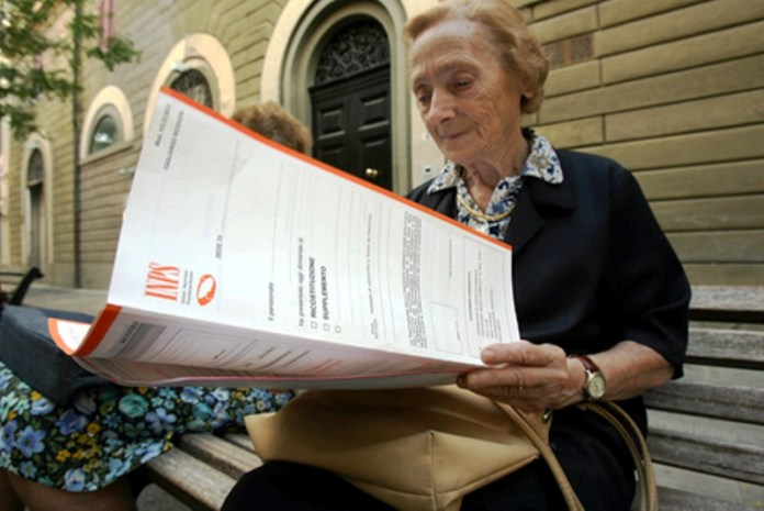 Una signora anziana legge una cartella dell'Inps - ANSA / FRANCO SILVI