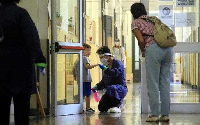 Riapertura Scuole , Scuola Materna di Via Brunacci, triage anti covid, commesse misurano la temperatura e disinfettano le scarpine dei bambini all ingresso, 07 settembre 2020, ANSA / PAOLO SALMOIRAGO
