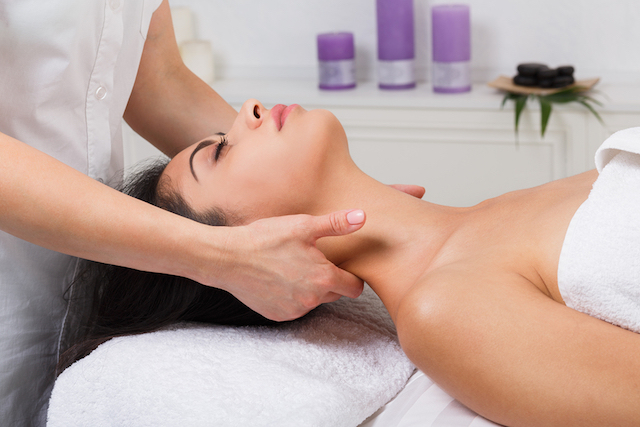 Unrecognizable female beautician doctor with patient in spa wellness center. Professional cosmetologist make body neck massage to beautiful indian girl in cosmetology cabinet or beauty parlor. FONTE IMAGE Goots