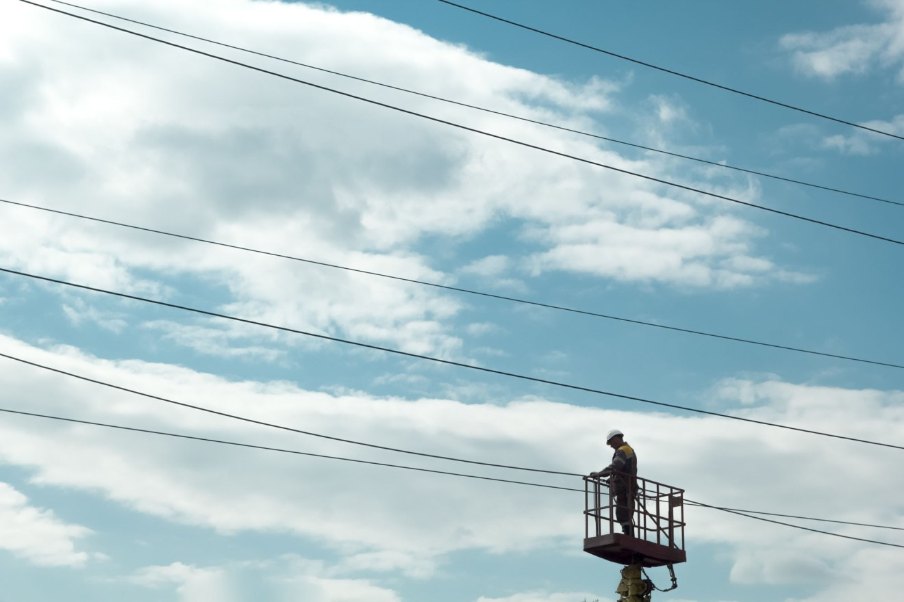 The electrician on the crane repairs high-voltage wires.