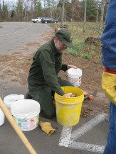 Robin Maercklein, Biologist/Chief of Resource Management for the St. Croix National Scenic Riverway, distributes seed into buckets for NPS staff and volunteers to spread at the site.