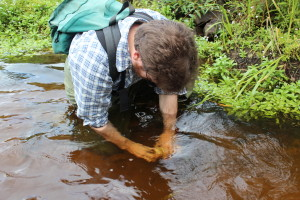 Patrick Shirey replaces a temperature logger in a spring-fed tributary of the Namekagon River