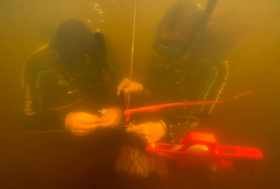 Divers attach markings and measuring tape to the St. Croix River structure as they prepare to carefully map its location and extent.