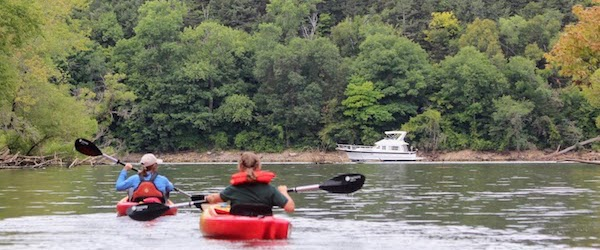 Mouth of the Kinnickinnic River with kayakers and a cabin cruiser