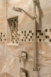 Glass and Stone Mosaic Tile adds detail to the 12X24 porcelain tiles on the shower walls.