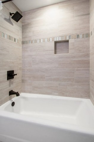 Beach tones bath has ceramic tile surround.