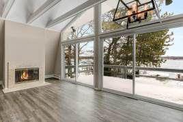Vinyl plank floors, bright walls and a cozy fireplace making the view inside the home as welcoming as the beautiful lake views from this space.