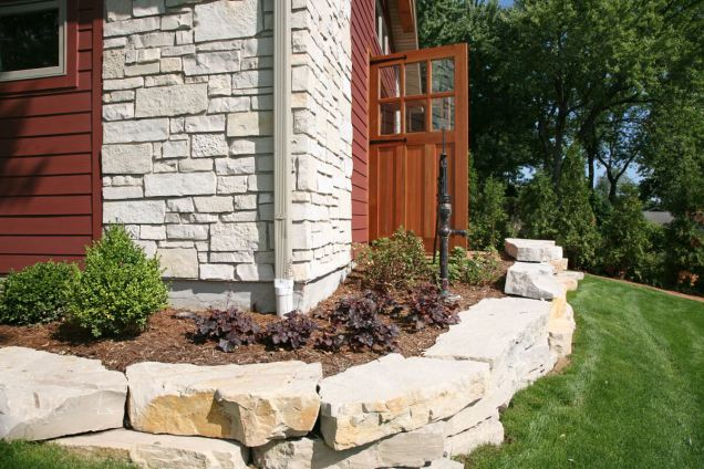 Custom crafted carriage doors open up to a crushed granite pathway.