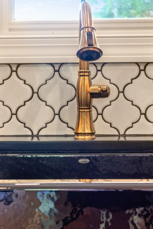 Black Kohler sink and a gold faucet add detail to this beautiful kitchen remodel