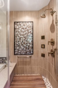 Large luxury shower features multiple shower heads and tile mosaic.