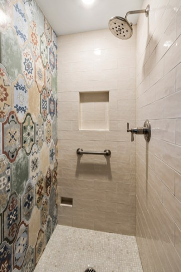 Tiled shower enclosure includes shampoo niche, toe kick and brushed nickel shower head