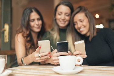 Friends at coffee shop watching social media