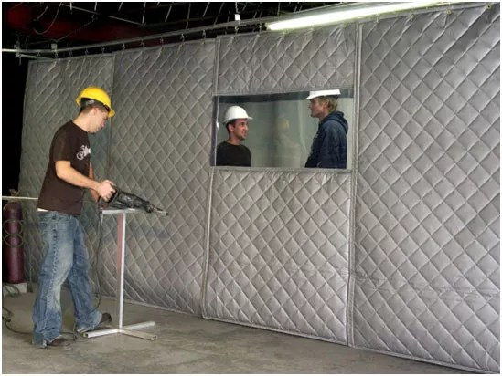a sound barrier curtain between warehouse workers