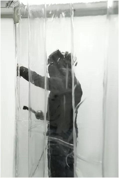 a worker behind vinyl strip doors