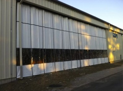 Industrial Outdoor Curtain on Exterior of Manufacturing Warehouse with Webbing Reinforcement and D-Ring Tie Down Straps
