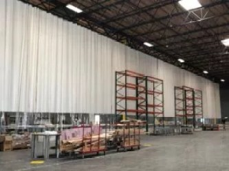 Warehouse Curtain Divider Containing Dust in Production Facility