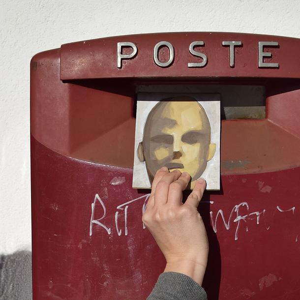 Una mano mette il ritratto di un uomo fatto su una cartolina nella cassetta della posta