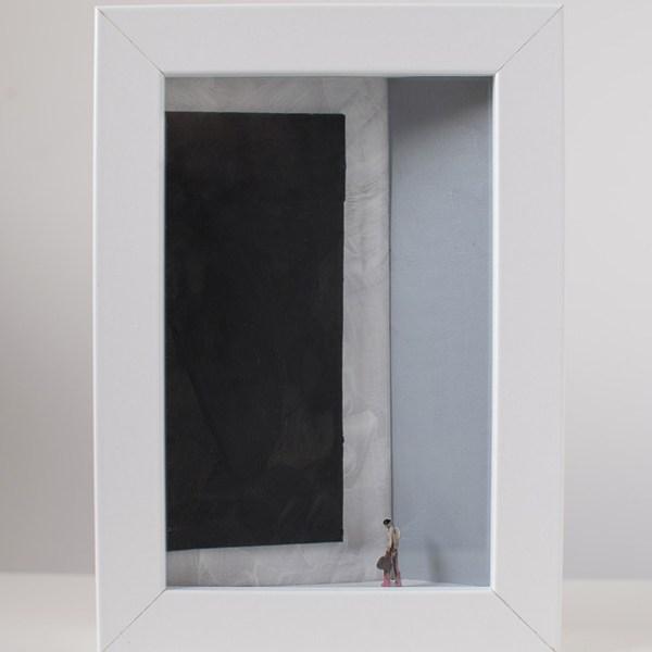 Un uomo con la valigia osserva un quadro nero monocromo