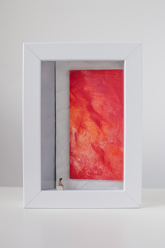 una donna seduta in una galleria d'arte osserva un quadro tutto rosso.