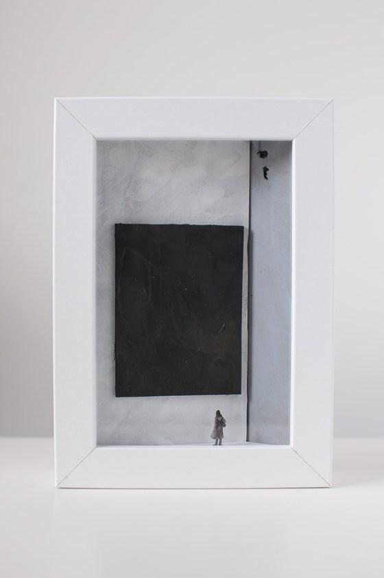 un quadro diorama rappresenta una donna che osserva un quadro tutto nero.