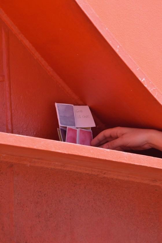 la mano dell'artista appoggia un dono d'arte su una struttura di ferro dipinta di rosso