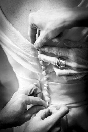 Dettaglio di mani che chiudono con attenzione l'abito da sposa.