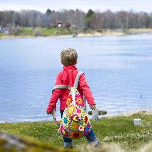 Mormorsrutor, virkad ryggsäck på barn utomhus vid vattnet, fotografering till bok. Fotograf Stefan Tell