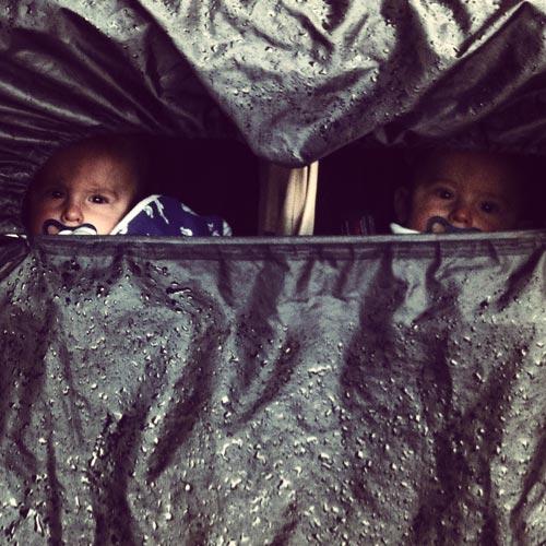 tvillingar-i-vagn-med-regnskydd-arga-blickar