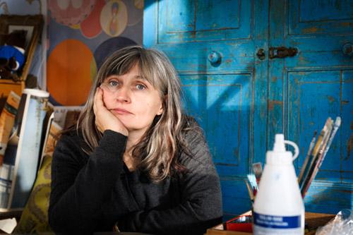Anna Höglund vid ett bord i sin ateljé, författarporträtt för Bonnier Carlsen, 2013. Fotograf Stefan Tell