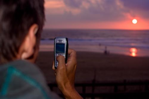 gammal-mobiltelefon-fotograferar-solnedgång