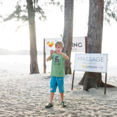 pojke-framfor-skylt-ving-sunwing-bangtao-resort