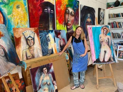 Steffi Goddard in her studio surrounded by her paintings of women