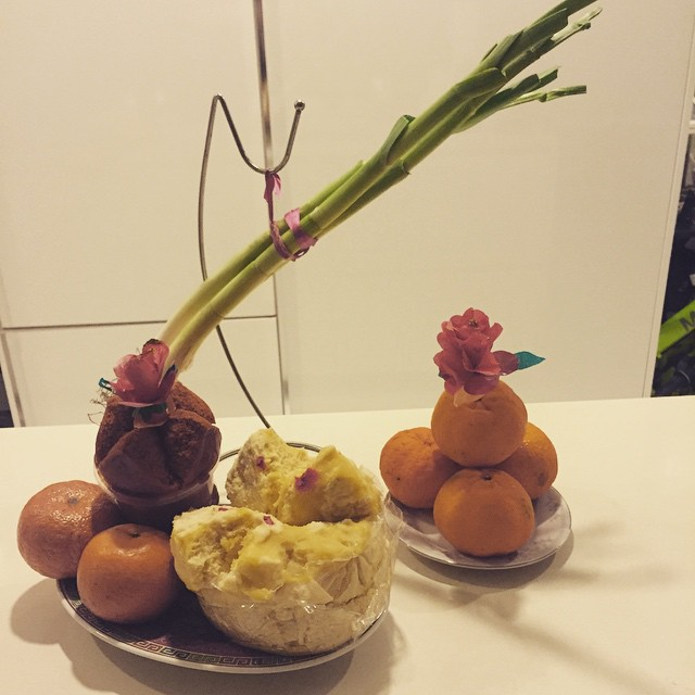 What's your CNY food tradition? In my family, my mum will personally prepare and gift each of her sons-in-law with this 'good luck set'. Leeks ('suan na' in Hokkien) are hung up so that our households will have plenty to 'count' in the new year. A brown store-bought Huat Kueh atop a Nian Gao (sticky cake; hidden from view), is topped with a Chun Huay (paper 'spring flower') to symbolize a 'huat' (flourishing) year ahead. An extra Chun Huay on a pyramid of mandarin oranges. The yellow steamed Huat Kueh dotted with red is my mum's homemade goodie to double the 'huat' (and because it's much yummier than store-bought ones). The whole set-up (minus the yellow Huat Kueh, which is for our eating pleasure) is left to Kia Ngee ('stand' from CNY eve throughout the Chinese New Year period of 15 days) so that it can grow mould. The more mould, the more 'huat'! My mandarin oranges are growing mouldy already!  Here's wishing all my friends, business associates, colleagues and students a very blessed, healthy and prosperous Year of the Sheep! #cny2015 #huatah #homemade