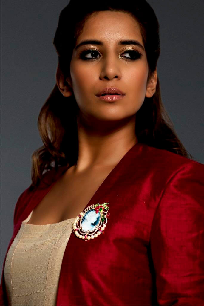 Model wearing a beautiful Brooch cum pendant in 18K gold featuring princess cameo of 40x30mm with diamonds, calibre cut and marquise shapes rubies and pearls, accentuated by french enamel.