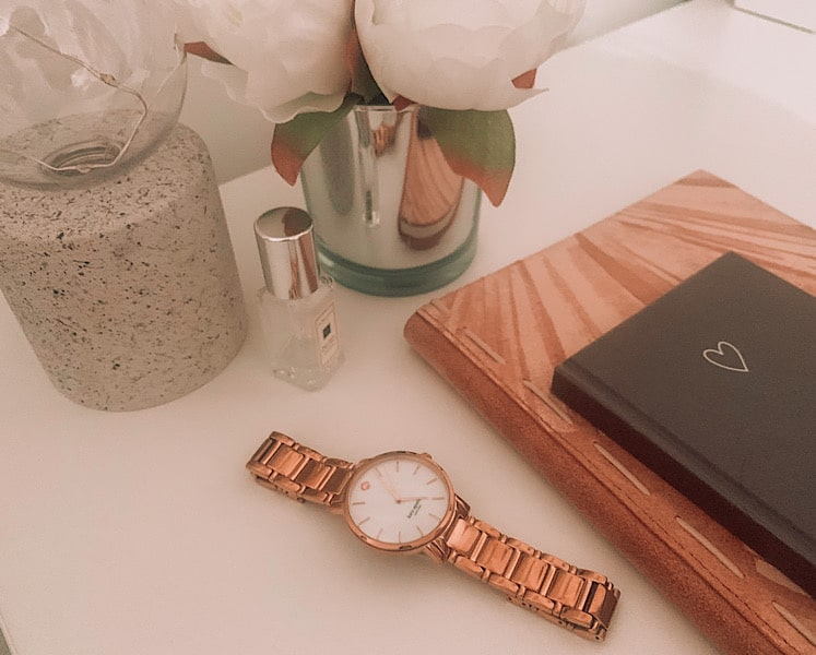 watch and notebooks on desk