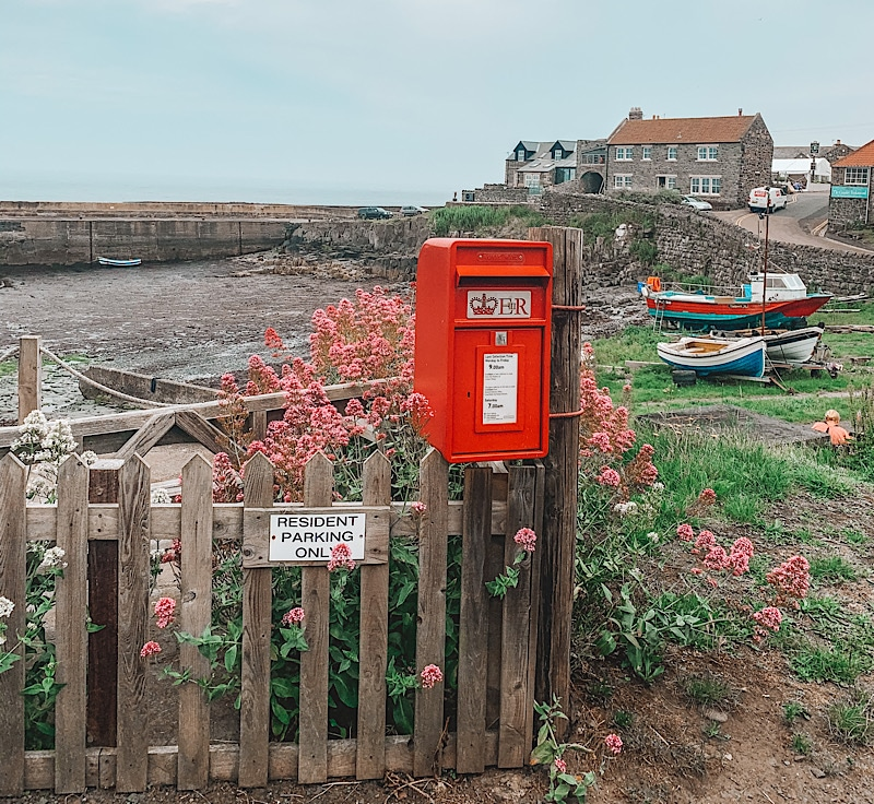 Post box and view of Craster harbour