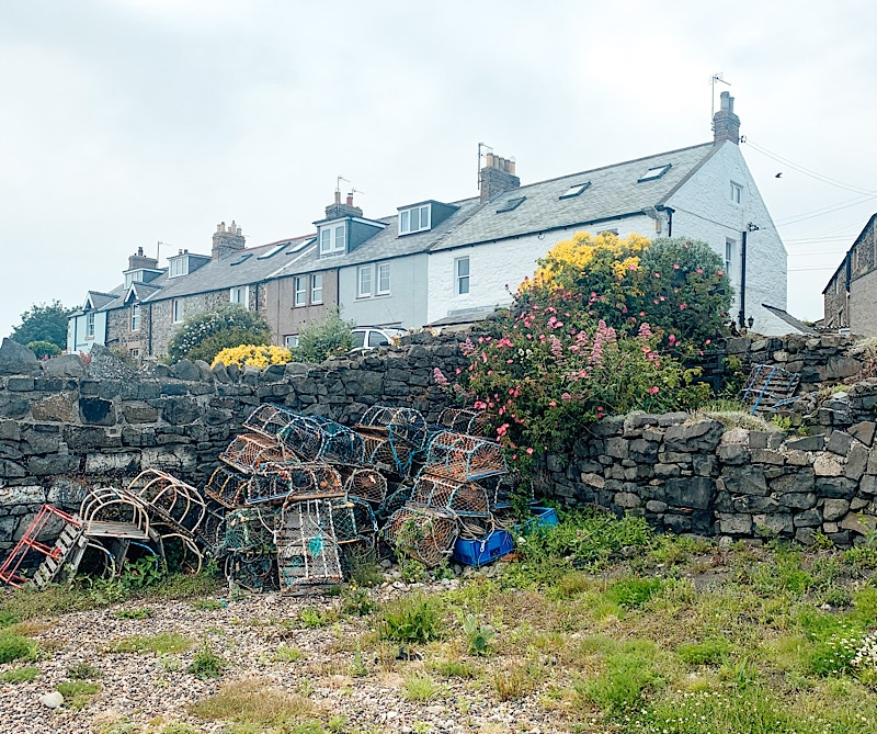 Lobster pots in front of holiday homes in Craster