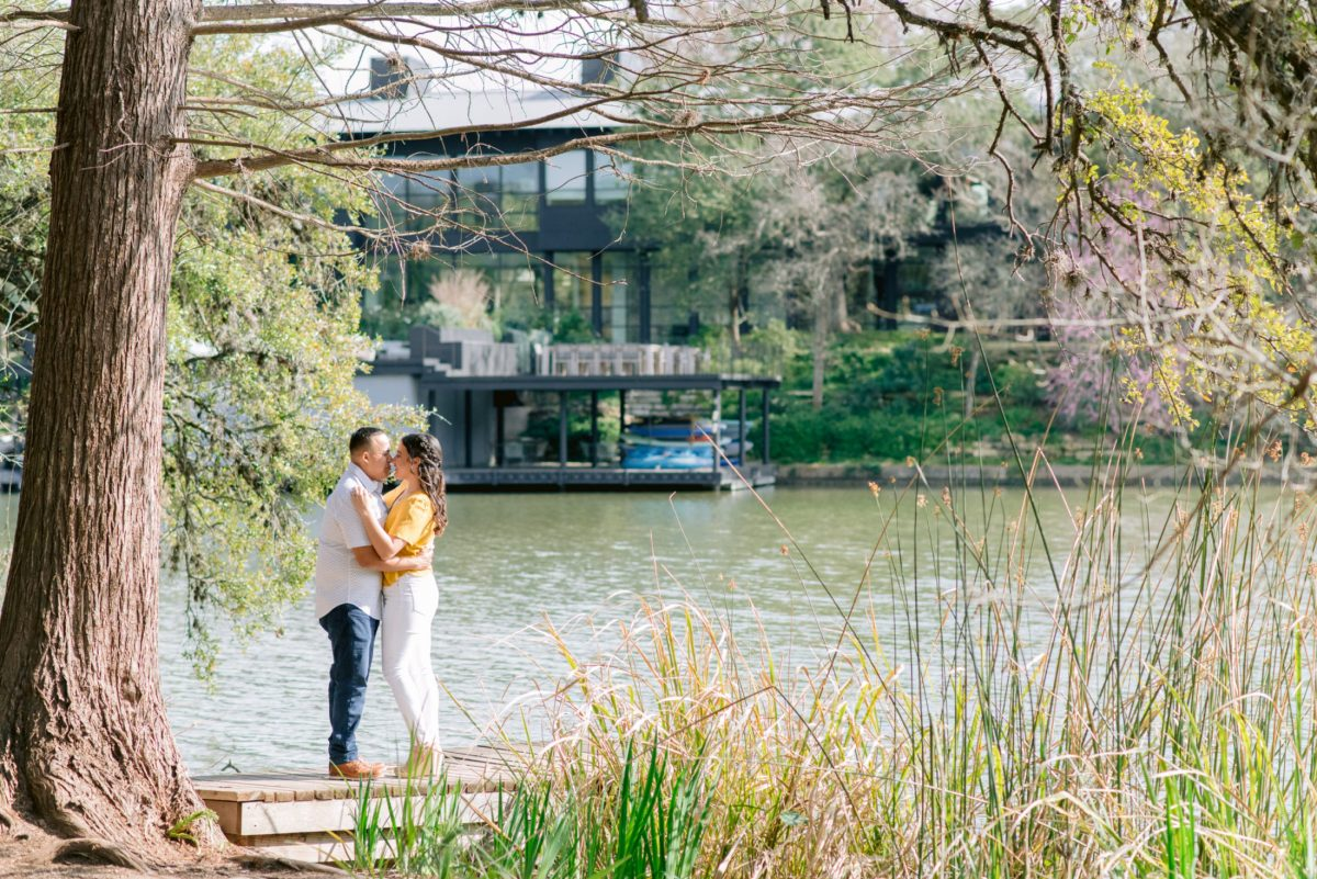 couple stands on dock of lakefront engagement session at laguna gloria