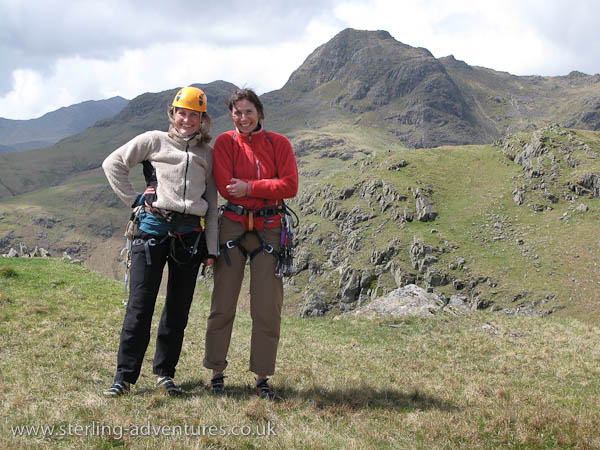 Mina and Laetitia feeling a bit chilled in the cold wind on top of White Ghyll, with Harrison Stickle behind