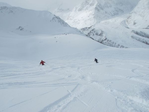 Pete and Jon riding the awesome powder towards the Val Veney far below.