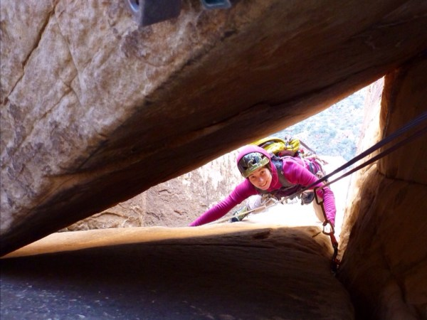 Laetitia about to squeeze behind the chockstone on pitch 5 on Frogland
