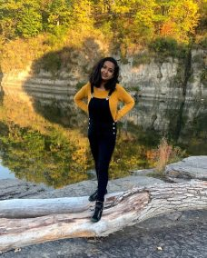 Photo of Anushka in a yellow sweater and black overalls standing and smiling on a fallen tree on the bank of a lake in Burlington, Vermont. Rocky cliffs and autumn foliage rise behind her. The scene is mirrored in the lake.