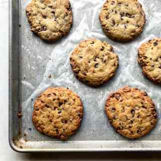 Picture of perfectly golden brown chocolate chip cookies cooling on a metal cookie sheet