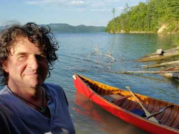 Sterling alum Bill Laity '90 poses in the foreground with the bright red Horace Strong canoe in the background. The photo was taken on a sunny day at a lake, with an island and mountains in the background.