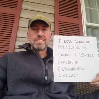 David is wearing a blue fleece and wearing a tan ballpark. He is holding a sign thanking Sterling for launching his career in environmental advocacy