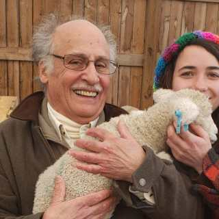 Rick is on the Sterling Farm holding a lamb and standing with a student in a plaid jacket