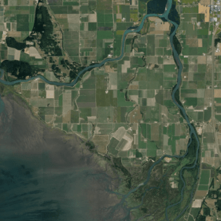 Aerial view of farmland with square patches of cultivated land. Branching river.