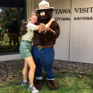 Abbey is wearing green shorts and a tshirt and hugging Smokey the Bear