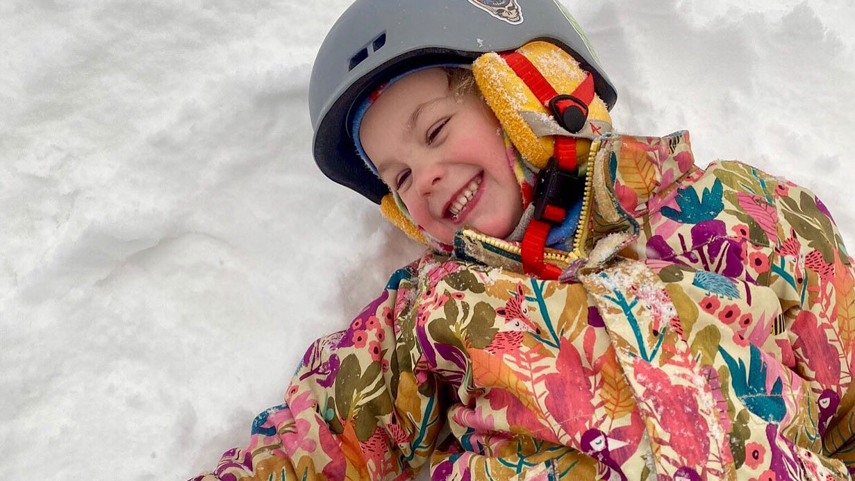 kids ski bundle - child in ski helmet laughing in snow | Sterling Ridge Log Cabin Resort