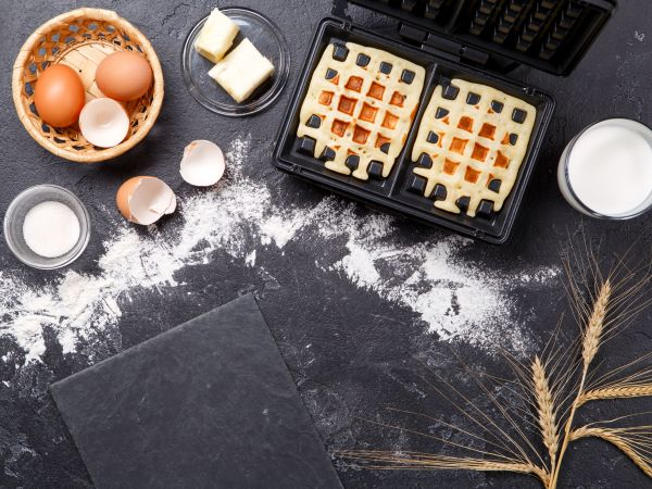 Photo on top of ingredients for viennese waffles, waffle iron, spikes, fried wafers on black table